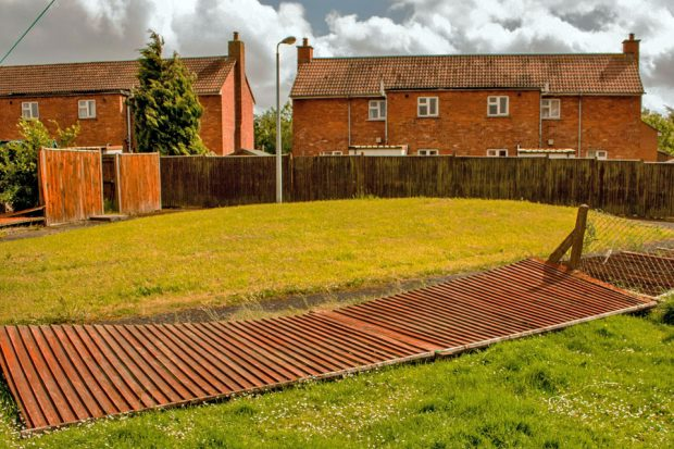 Suburban fence panels have fallen down, making the boundary unclear.