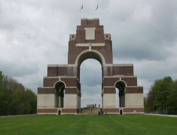 The Thiepval Memorial against a cloudy sky with a green lawn in front.
