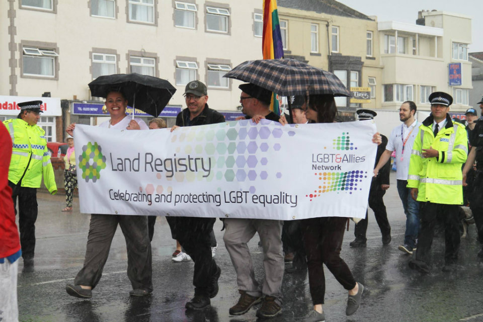 Emma and her colleagues walking behind a Land Registry banner at Blackpool Pride.