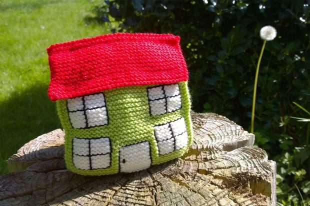 A knitted house sitting on top of a tree stump.