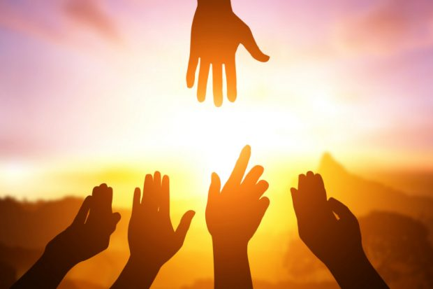 Hands reaching out to each other, with bright sunshine in the background.