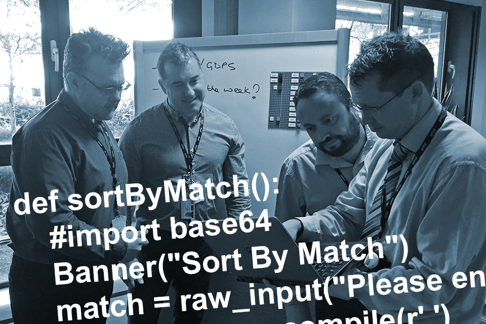 Four men collaborate around a laptop screen with text superimposed signifying complex technical language.