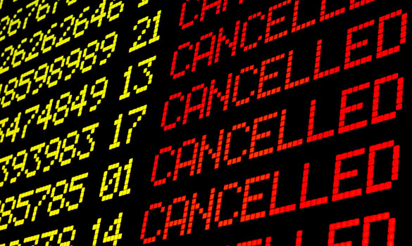 Cancelled flights on airport board panel.