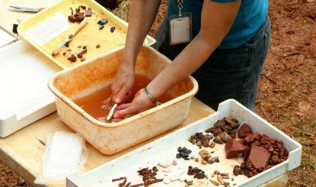 An archaeologist washes an artifact excavated at a dig.