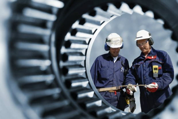 Two engineers at work, viewed through a cog wheel.