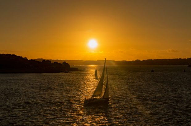 A sailing boat sets out in evening sunshine.