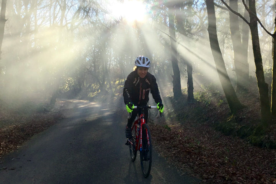 Rachel Jones cycling through woodland, with dappled light through tress