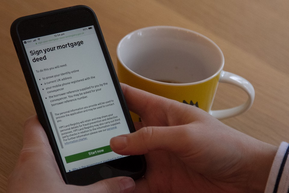 A hand holds a mobile phone showing the Sign your mortgage deed service on its screen, with a coffee mug on the desk alongside.