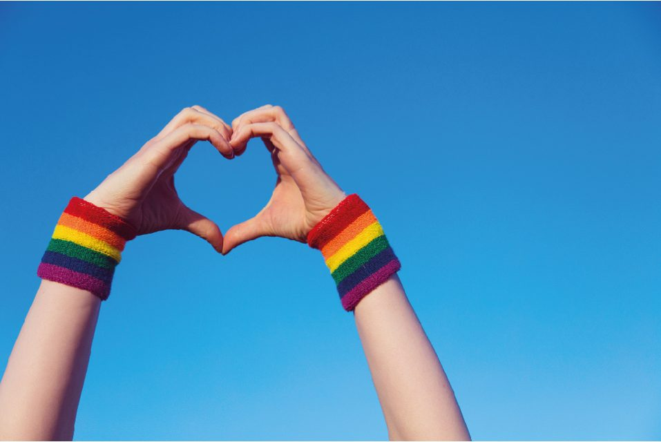 Two hands forming a heart shape with rainbow wristbands around the wrists.