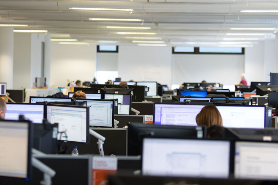 Rows of screens in an office with people working at them.