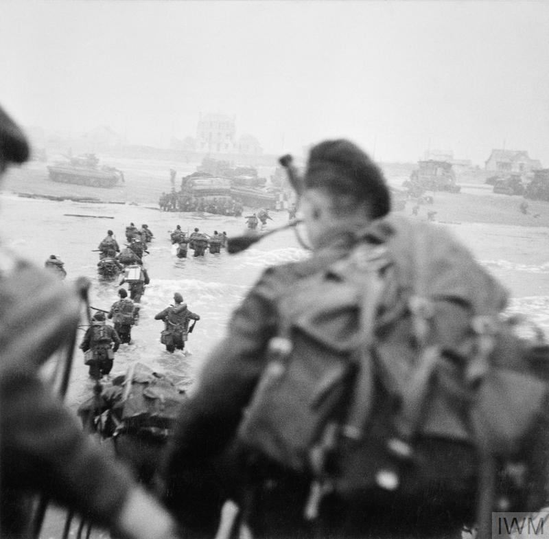 Commandos disembark from a landing craft onto a beach.