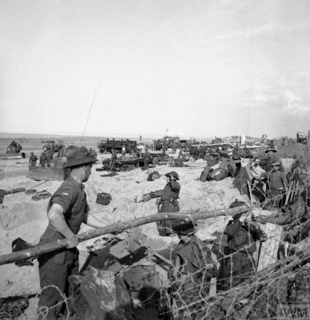 Troops digging in on a beach.