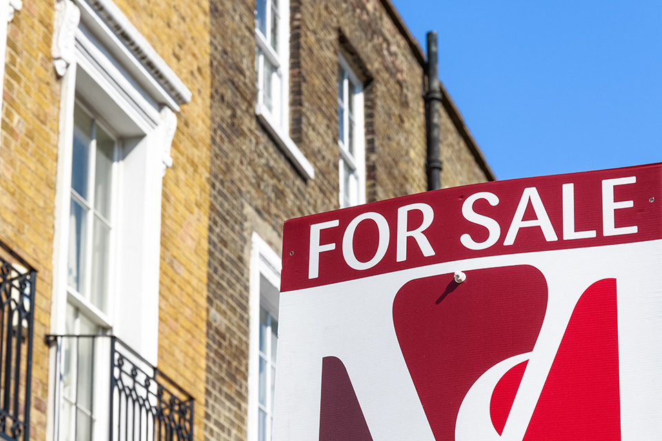 Photo of a 'For sale' sign in front of a terrace of houses.