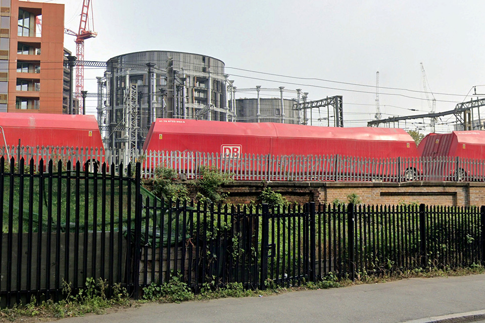 Gas holders converted into homes behind a railway line and a fence.
