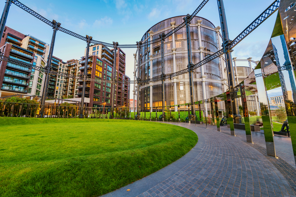 A gasholder converted into homes viewed through the frame of a neighbouring gasholder turned into a park.