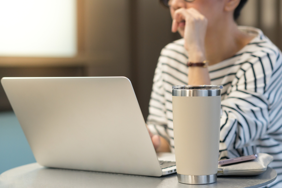 An office worker using a laptop with a reusable stainless steel tumbler mug alongside.